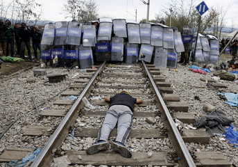 Iranian migrant lies in front of Macedonian police at the Greek-Macedonian border