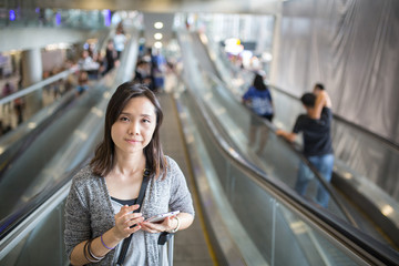 Asian woman look and search her fight with mobile phone