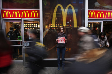 A member of 'MoveOn' holds up a poster during a protest in front of McDonald's restaurant in Times Square, New York