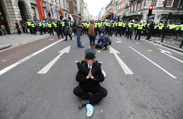 Demonstrators sit down on Piccadilly during a protest organised by the Trades Union Congress,  in central London