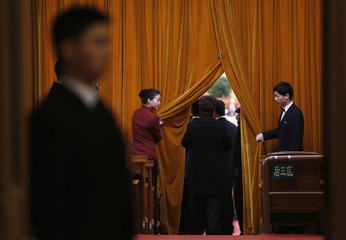 Attendants raise curtains inside Great Hall of the People ahead of fourth plenary meeting of National People's Congress in Beijing