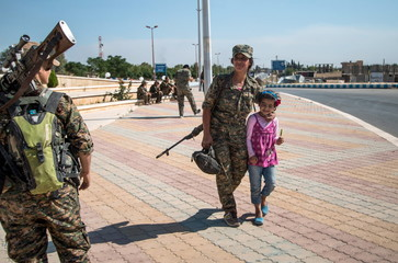 A YPG fighter walks with a girl in Tel Abyad town