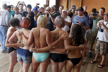 """Topless activists pose for photographs for onlookers during a """"Free the Nipple"""" demonstration in Hampton Beach"""