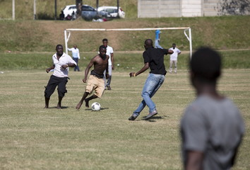 Foreign men play soccer at a camp for those affected by anti-immigrant violence in Chatsworth