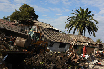 Workers clean up debris after a major earthquake and ensuing tsunami caused massive destruction in Constitucion