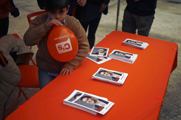 A child inflates a balloon next to a table with pictures of Ciudadanos party leader Rivera during an election campaign rally in Cadiz