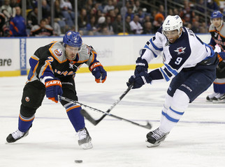 Winnipeg Jets goalie Evander Kane fights for the puck with the New York Islanders Mark Streit during the second period of their NHL hockey game in Uniondale, New York