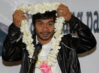 Filipino boxing icon Manny Pacquiao removes his garland of flowers before he delivers his speech upon his arrival arrival at the Ninoy Aquino International Airport in Manila
