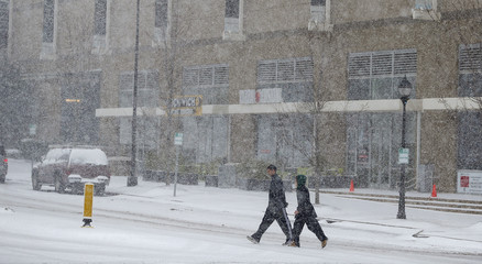 Two pedestrians make their way across a street as snow continues to fall in Charlotte