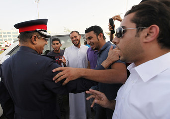 A police officer speaks to anti-government protesters as he stops them from marching during a demonstration outside Bahrain's leading opposition party Al Wefaq's headquarters in Manama