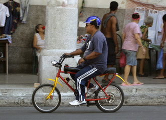 A man rides a petrol powered bicycle in Havana