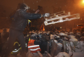 A man throws a wooden tray as riot police gather near a barricade set up by supporters of EU integration in Kiev
