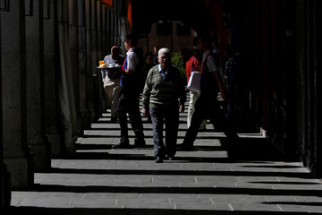 A waiter carries a tray at Plaza Mayor, one of the city's main touristic areas, in Madrid