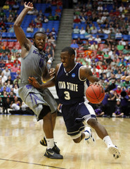 Aggies' Pane drives on Wildcats' Pullen during the second round NCAA tournament basketball game in Tucson