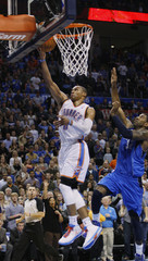 Thunder guard Westbrook scores against  Mavericks guard Mayo in the overtime period of their NBA basketball game in Oklahoma City
