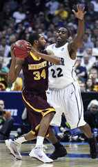 Minnesota's forward Johnson looks to pass against Xavier's forward McLean during the second half of their NCAA Division I Men's Basketball Tournament game in Milwaukee