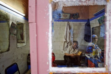 A woman is reflected in the mirror of shop as a barber reads the Koran in Rabat's Medina