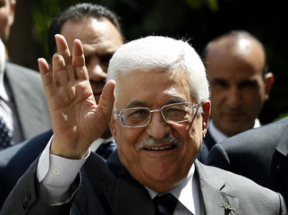 Palestinian President Abbas waves to the media as he arrives for an Arab League Foreign Ministers emergency meeting in Cairo
