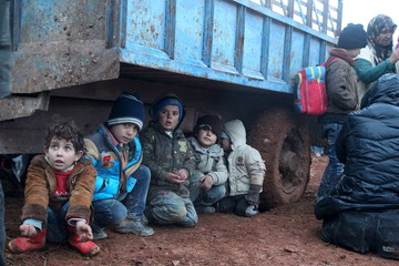 Displaced children, who fled with their families the violence from Islamic State-controlled area of al-Bab, wait as they are stuck in the Syrian village of Akda to cross into Turkey