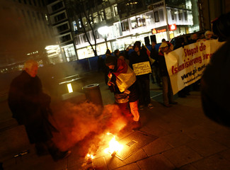 PEDGIDA protestors try to extinguish a flare during a demonstration in Frankfurt