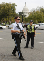 A United States Park Police officer with an automatic weapon secures the scene of a shooting in front of the U.S. Capitol on Capitol Hill in Washington