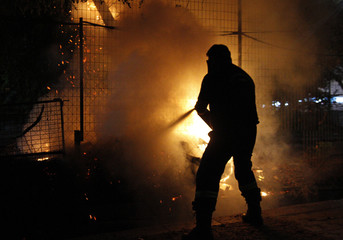 A firefighter extinguishes a fire set by unknown rioters during a violent demonstration against austerity in Thessalonik