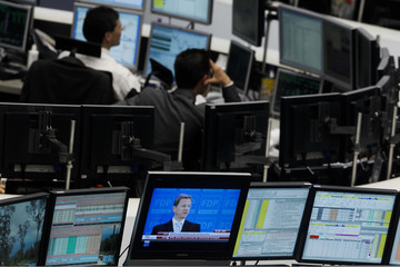 Trader are pictured at their desks next to a TV screen showing Westerwelle at the Frankfurt stock exchange