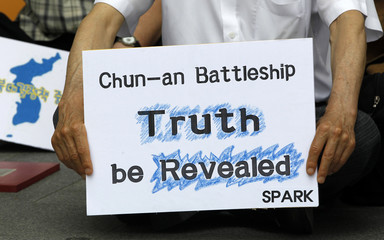 A pro-unification and anti-war activist holds a placard during a rally commemorating the 10th anniversary of the June 15 declaration between the two Koreas, in Seoul