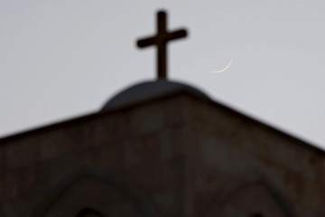 A cross on a Lutheran Church is pictured with the moon in the background during a celebration of the lighting of a 12-metre-tall Christmas tree in Shouneh