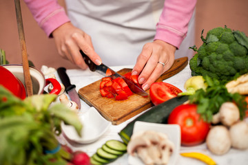 Woman cutting tomato on slices on chopping board