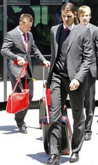 Bayern Munich's Daniel van Buyten and Ivica Olic carry their belongings upon arrival at Madrid's Barajas airport
