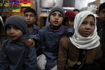Students from underprivileged background listen to their teacher explain how to use a computer at Mashal School on the outskirts of Islamabad