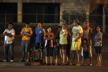Residents look at a crime scene where two people were gunned down at a bar in Monterrey