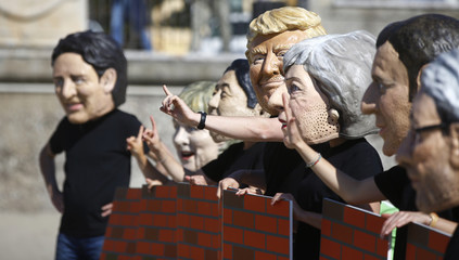 3a4d828ceb3 Protesters wear masks depicting the leaders of the G7 countries during a  demonstration organised by Oxfam