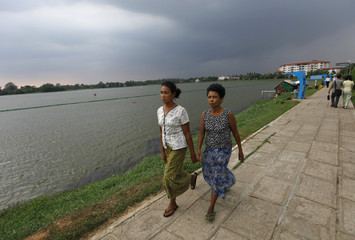 Women walk along the Inya Lake bank as rain clouds gather over the skyline in Yangon