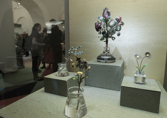 Visitors walk past a display of flowers made from precious stones in the Kremlin