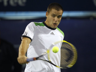 Youzhny of Russia hits a return to Simon of France during their match at the ATP Dubai Tennis Championships