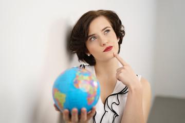 studentin mit weltkugel schaut nachdenklich nach oben und plant einen auslandsaufenthalt