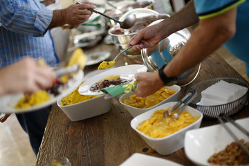 Guests are seen filling their dishes with typical Brazilian food while watching the round of 16 soccer match for the 2014 World Cup between Chile and Brazil at a gathering in a home in the upper class neighborhood of Lago Sul in Brasilia