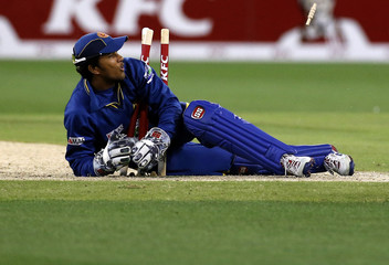 Sri Lanka's wicketkeeper Dinesh Chandimal lies on the stumps after attempting a run out during the Twenty20 international cricket match against Australia at the Melbourne Cricket Ground