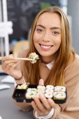 junge frau isst sushi in der pause im büro