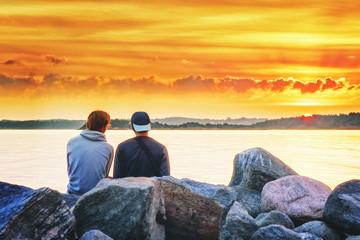 Two boys sitting at stones of Northern sea shore looking at breathtaking sunset sky. Rear view. Sweden, Europe. Fellowship background.