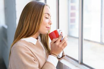 selbstbewusste junge frau genießt eine tasse tee