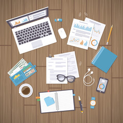 Office work place with documents, laptop, notebook, wallet, phone, watch, glasses, pencil, pen,  graphs and charts, headphones, coffee, forms. Wooden desk with supplies. Organization, management.