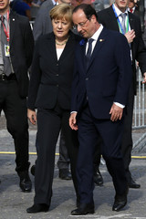 Germany's Chancellor Merkel talks to France's President Hollande as they arrive for a family photo after a ceremony to commemorate the centenary of the start of World War I, in Ypres