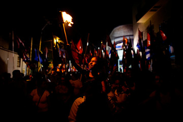 Anacarla Arasay holds a torch during a march in celebration of the 164th birth anniversary of Cuba's independence hero Jose Marti in Havana, Cuba