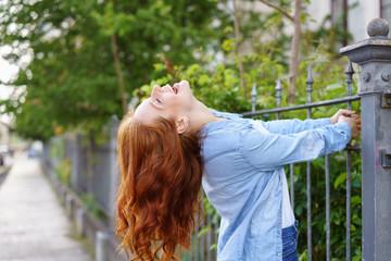 lachende frau hält sich an einem zaun fest und lacht