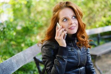 frau sitzt im park und telefoniert