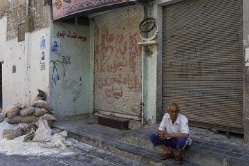 A man sits on the steps outside a shop in the old city of Alepp