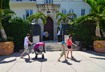 People walk by the South Beach mansion formerly owned by fashion designer Gianni Versace in Miami Beach